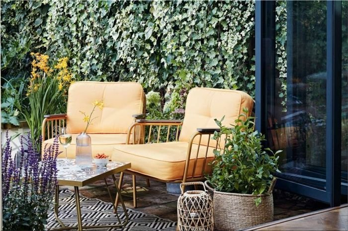 Beautiful, well-landscaped garden - yellow armchairs, green plants and flowers