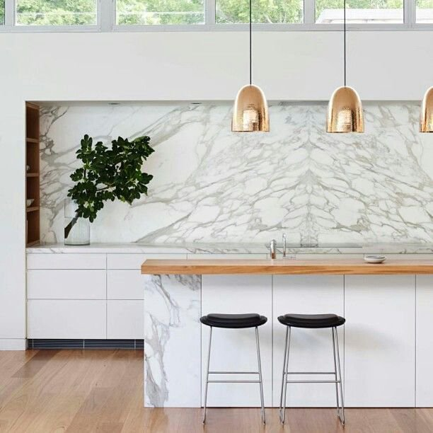 marble kitchen with brass pendant lights